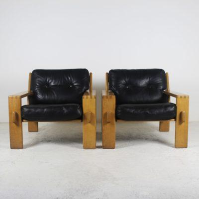 Paire de fauteuils scandinaves vintage 1960, en chêne et coussins en cuir noir.