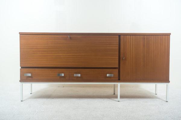 Enfilade vintage années 1960 par Antoine Philippon et Jacqueline Lecoq, structure en acajou s'ouvrant par deux portes et tiroirs en façade, poignées en métal, piétement en métal laqué blanc.