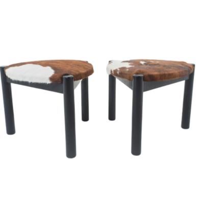 paire de tabourets tripodes vintage des années 60, piétement en bois noir, assises recouvertes de peau de vache.