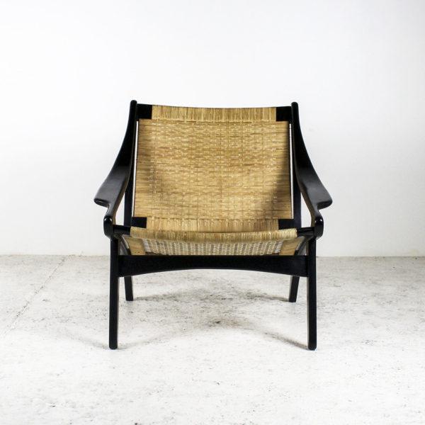 Fauteuil rétro des années 50, assise en rotin, piétement en bois laqué noir.