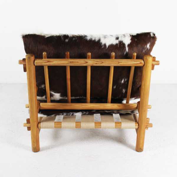 Fauteuil vintage des années 60, en bois de mélèze et coussins en peau de vache.