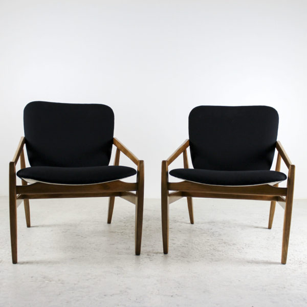 Fauteuils italiens vintage années 60, structure en bois et assises en tissu noir.