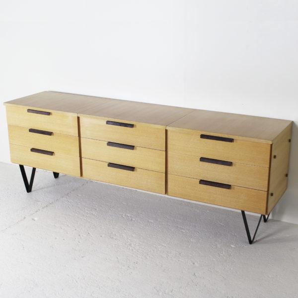 Commode vintage à neuf tiroirs, des années 50, structure en frêne, poignées et pieds en métal brun.