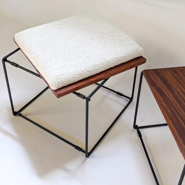 Paire de tables basses/tabourets vintage, à plateaux réversibles en acajou, coussin en mousse refaite à neuf, recouverte d'un tissu de la Maison Pierre Frey, piétement en métal laqué noir. Travail français des années 50.