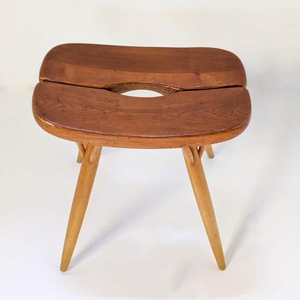 """Tabouret modèle """"Pirkka"""" du designer finlandais Ilmari Tapiovaara pour Laukaan Puu, produit vintage réalisé dans les années 50. L'assise en pin repose sur quatre pieds en bouleau, signatures du designer et du fabricant sous l'assise."""