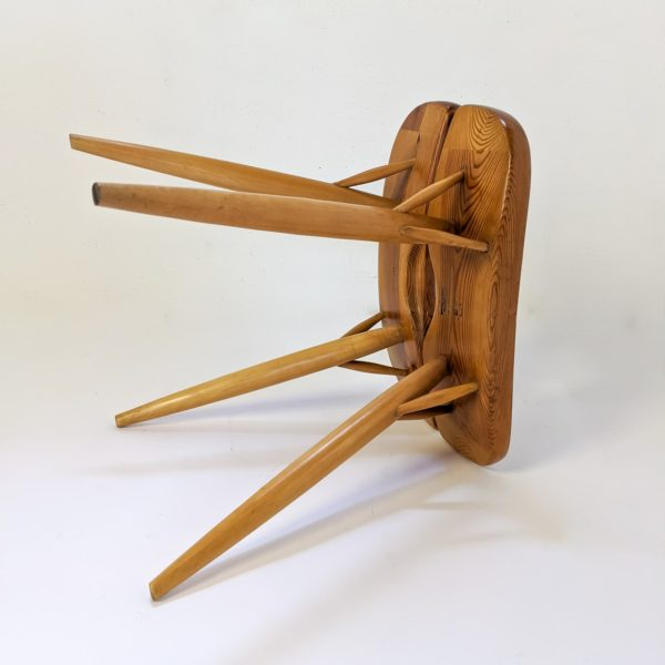"""Tabouret modèle """"Pirkka"""" du designer finlandais Ilmari Tapiovaara pour Laukaan Puu, modèle vintage réalisé dans les années 50. L'assise en pin repose sur quatre pieds en bouleau, signatures du designer et du fabricant sous l'assise."""