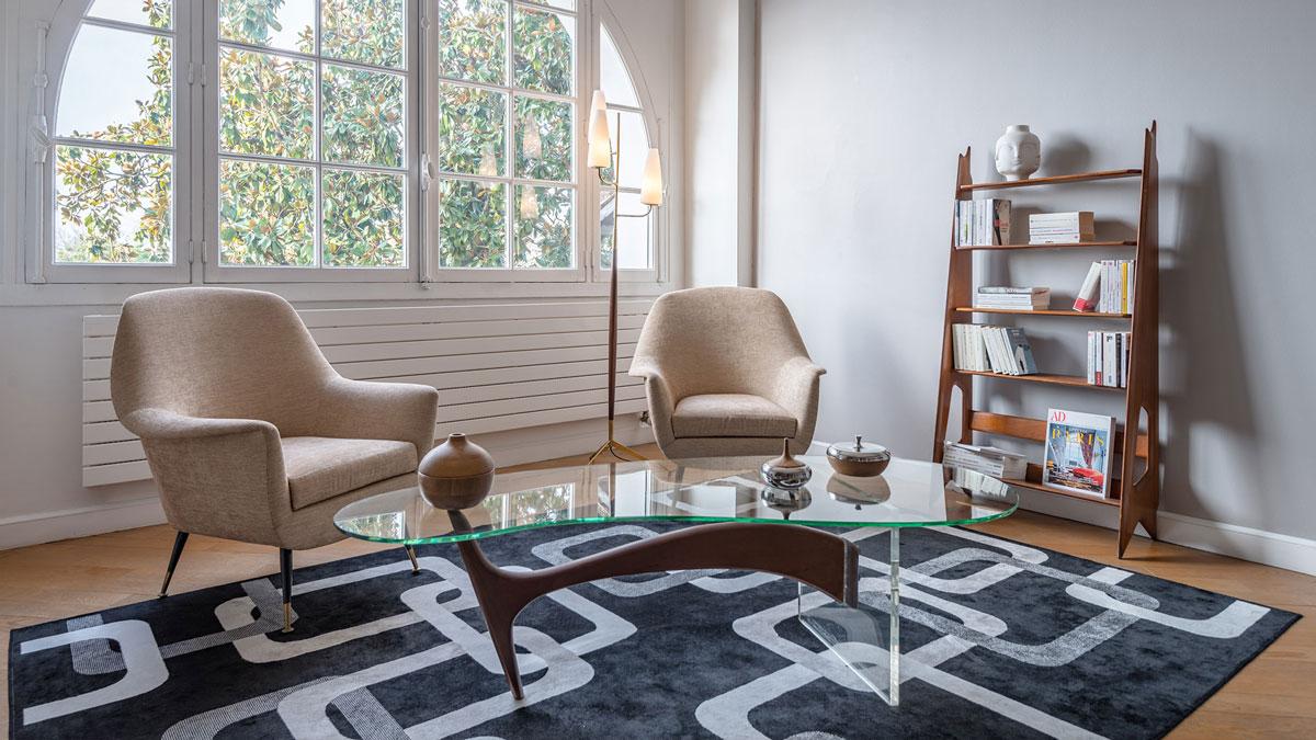 Décoration intérieure d'une maison, déco vintage chic, mobilier des années 50, lampadaire Lunel, table de forme libre en bois, plexis et verre, bibliothèque de Pierre Cruège.