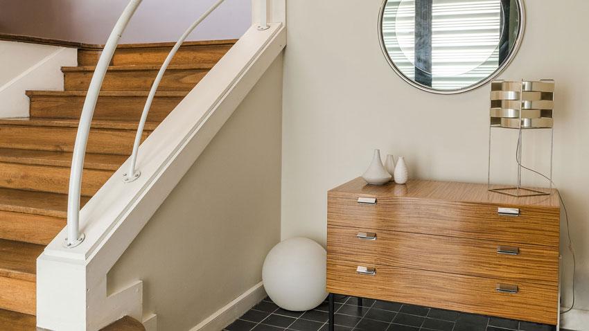 Décoration d'une maison, décor vintage avec une commode années 50 d'André Monpoix et miroir rond en verre années 70.